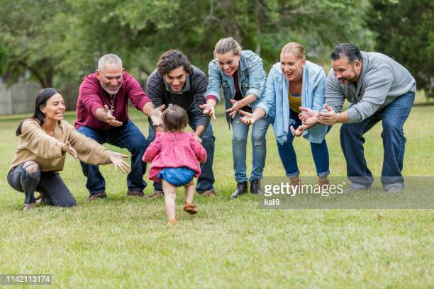 multi-generation hispanic family, baby walking toward - aunt stock pictures, royalty-free photos & images