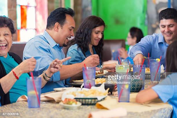 Multi-generation Hispanic family enjoying meal in casual restaurant
