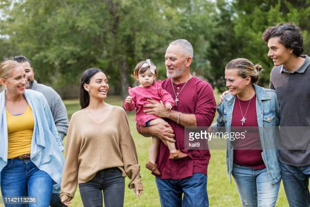 multi-generation hispanic family, looking at baby girl - family reunion stock pictures, royalty-free photos & images