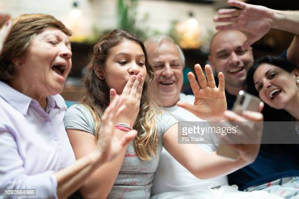 multi-generation hispanic-latino family having a video chat at home - spanish and portuguese ethnicity stock pictures, royalty-free photos & images
