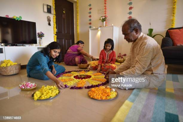 multi-generation indian family making floral rangoli for diwali celebration - flower part stock pictures, royalty-free photos & images