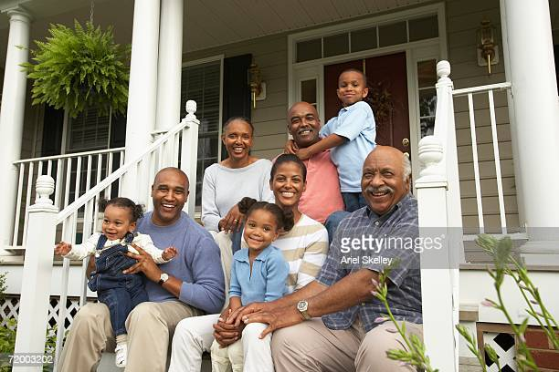 multi-generational african family smiling on porch - family reunion stock pictures, royalty-free photos & images