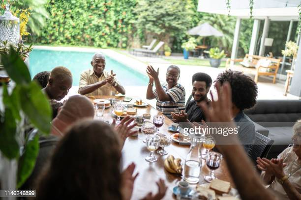 multigenerational family applauding during breakfast - family reunion stock pictures, royalty-free photos & images