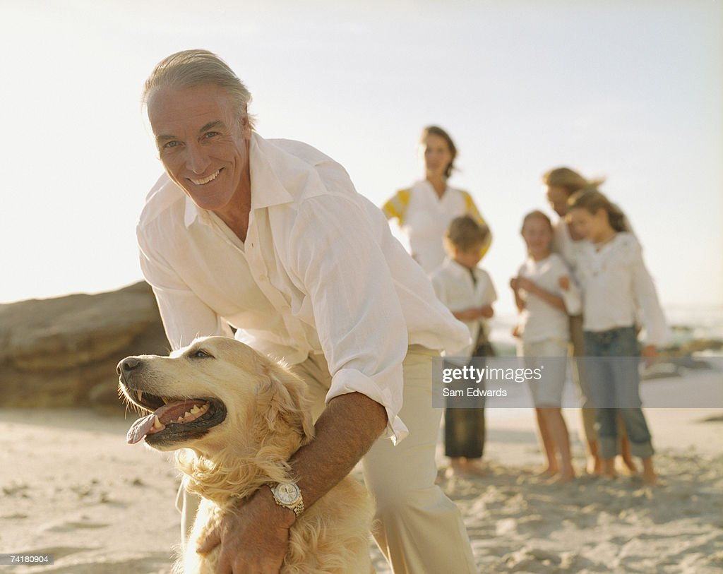 Multigenerational family at beach with dog : Stock Photo