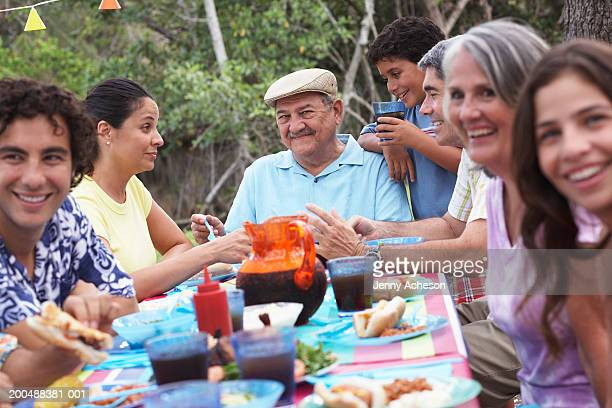 Multi-generational family dining outdoors, smiling