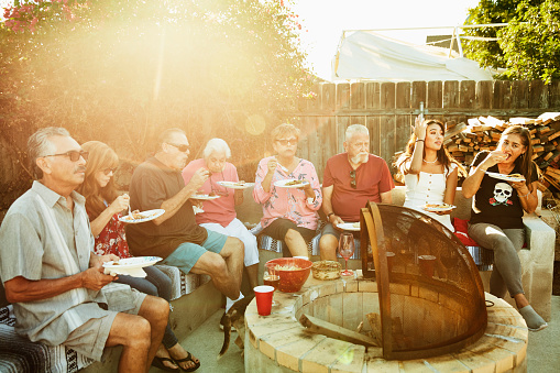 Multigenerational family dining together during backyard barbecue - gettyimageskorea