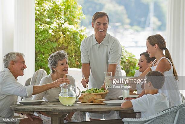 Multi-generational family eating on porch