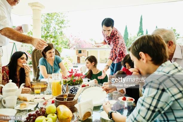 multigenerational family gathered for outdoor brunch - brunch stock pictures, royalty-free photos & images