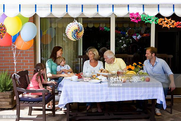 A multi-generational family having a celebration breakfast, outdoors