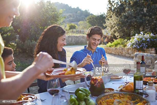 multigenerational family laughing at dinner - klaus vedfelt mallorca stock pictures, royalty-free photos & images