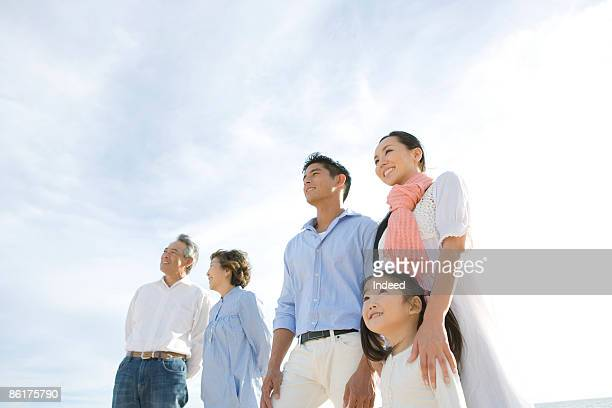 Multigenerational family looking at view on beach