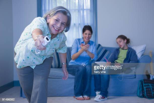 Multi-generational family playing video game