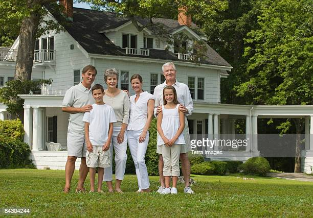 Multi-generational family posing in front yard