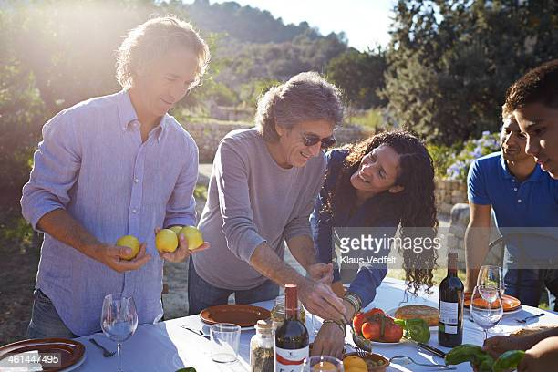 multigenerational family preparing dining table - klaus vedfelt mallorca stock pictures, royalty-free photos & images