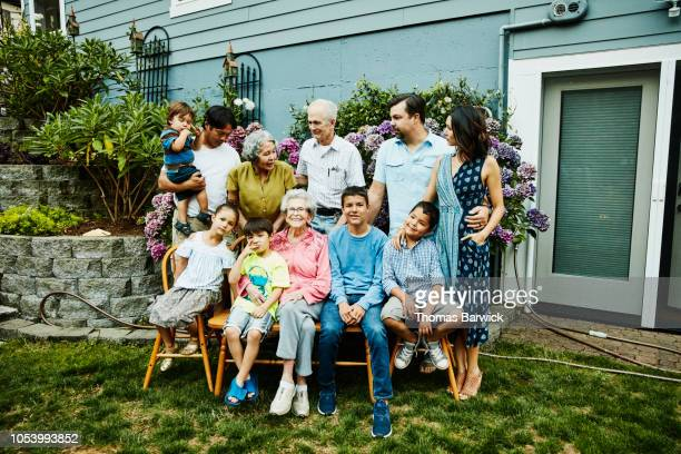 multigenerational family preparing for family portrait in backyard garden - great grandmother stock pictures, royalty-free photos & images
