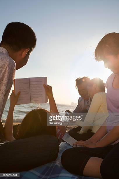 Multigenerational family relaxing and reading on the beach