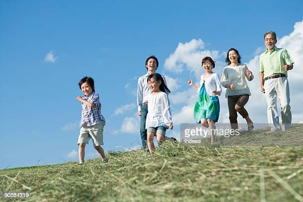 Multi-generational family runnning on grass