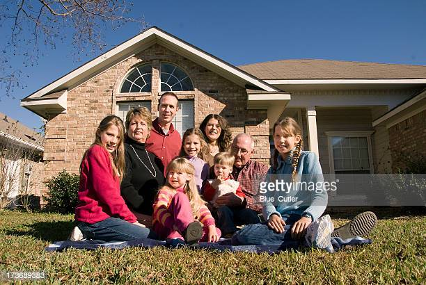 Multi-generational family sitting on front lawn