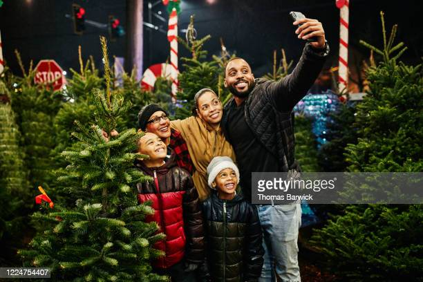 multigenerational family taking selfie while shopping for christmas tree - public celebratory event stock pictures, royalty-free photos & images