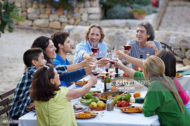 Multigenerational family toasting at dinner party