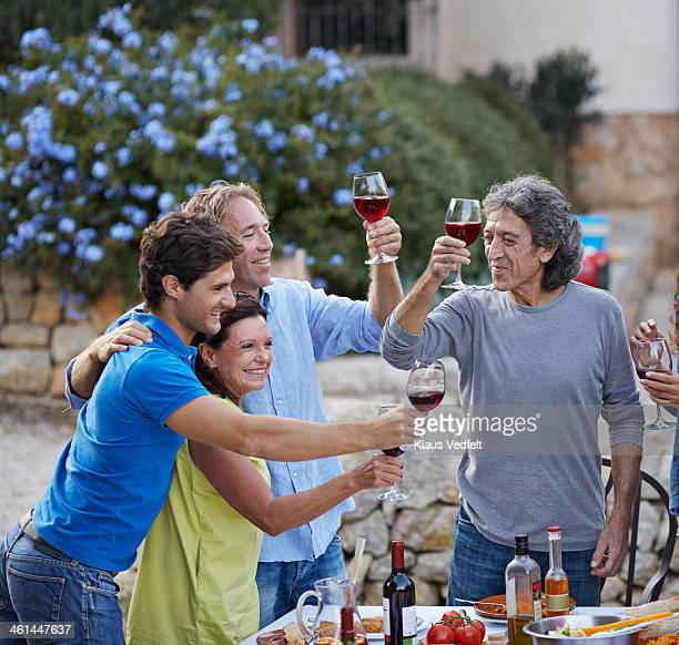 multigenerational family toasting at dinner party - klaus vedfelt mallorca stock pictures, royalty-free photos & images