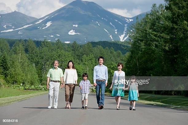 Multi-generational family walking, hoding hands