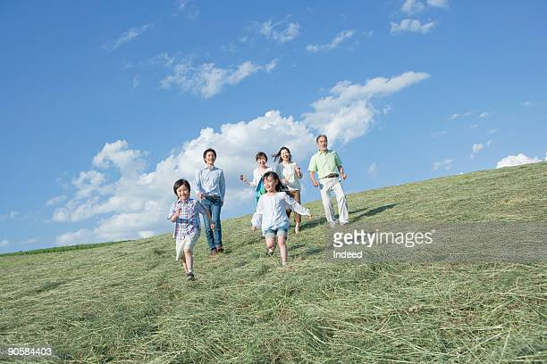 Multi-generational family walking on grass
