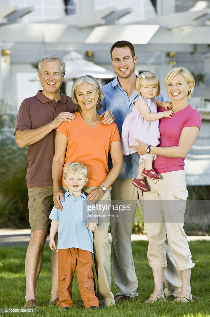 Multigenerational family with baby girl (9-12 months) and son (2-3 years) in front yard : Foto stock