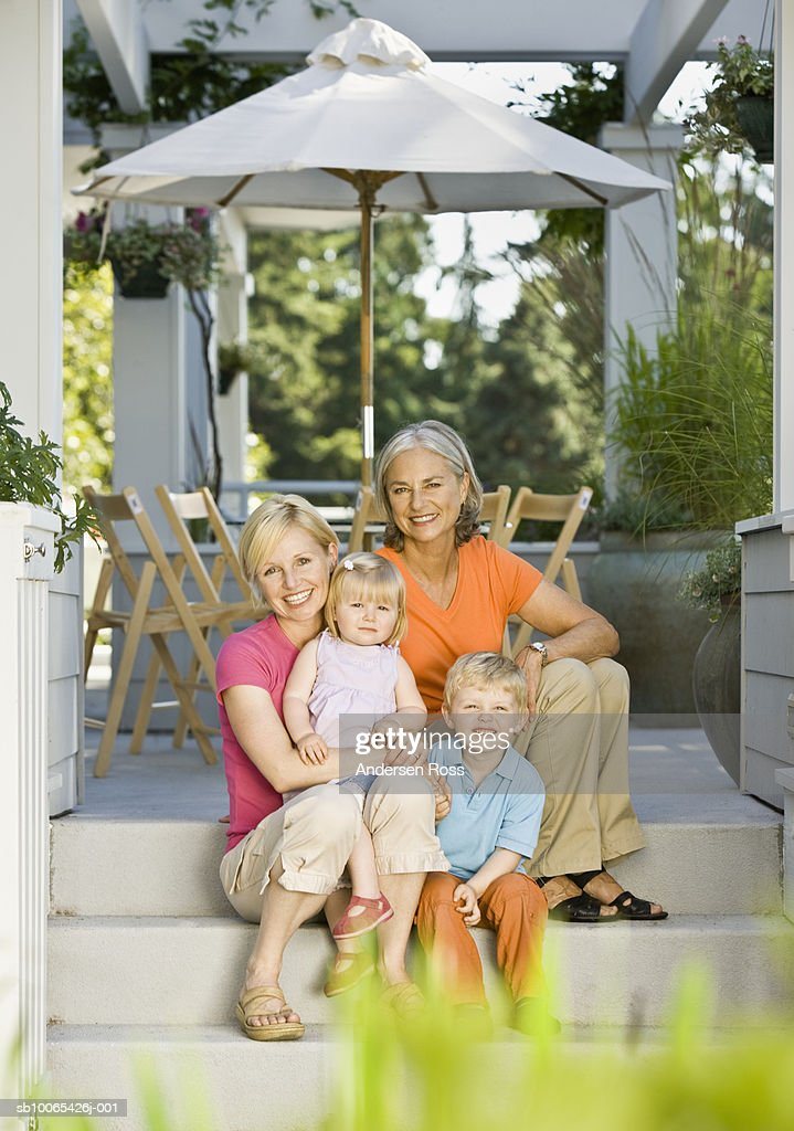 Multigenerational family with baby girl (9-12 months) and son (2-3 years) sitting on porch : Foto stock