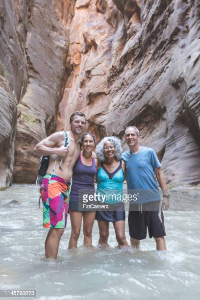 multigenerational hikers wading through a slot canyon - small group of people stock pictures, royalty-free photos & images