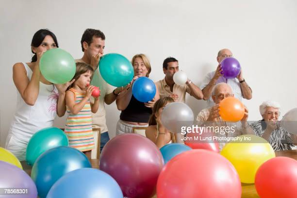 Multi-generational Hispanic family blowing up balloons