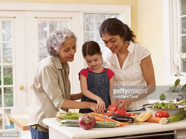 Multi-generational Hispanic family cooking in kitchen