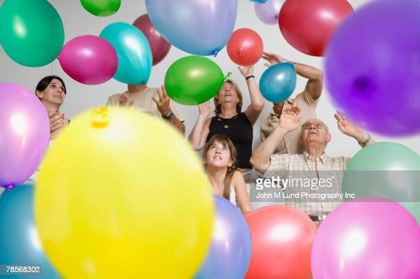 Multi-generational Hispanic family surrounded by balloons
