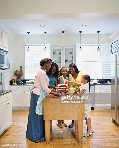 Multi-generational women deocrating cake in kitchen, side view