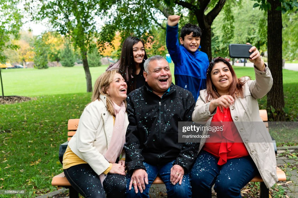Multi-generations Latin American family selfie outdoors. : Stock Photo