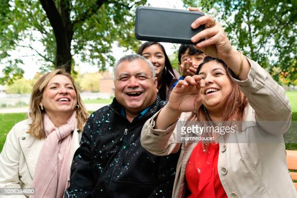 Multi-generations Latin American family selfie outdoors.