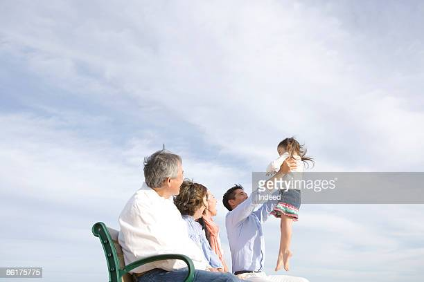 Multignerational family relaxing on bench