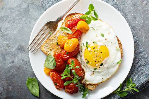 Multigrain toast with fried egg and roasted tomatoes 1036880806