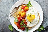 Multigrain toast with fried egg and roasted tomatoes