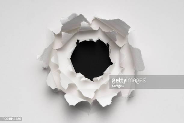 multi-layered white paper hole - agujero de bala fotografías e imágenes de stock