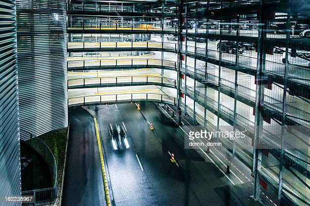multi-level covered parking garage with parking lofts, at night - construction platform stock photos and pictures
