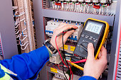 multimeter is in hands of engineer in electrical cabinet. Adjustment of automated control system for industrial equipment control cabinets. electrician measures voltage by tester.
