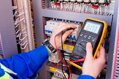 multimeter is in hands of engineer in electrical cabinet. Adjustment of automated control system for industrial equipment control cabinets. electrician measures voltage by tester. 946024888