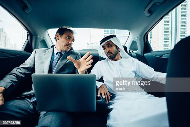 Multinational business discussion in a car