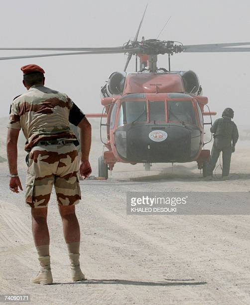 Multinational Force and Observers helicopter and personnel work at the site of the French military transport aircraft crash at the village of Biat...
