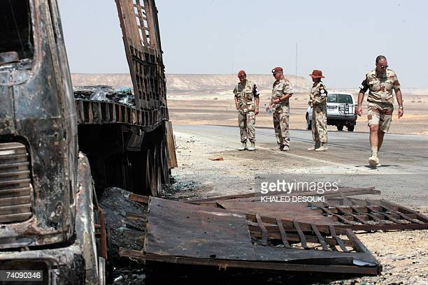 Multinational Force and Observers personnel inspect the site of a burnedout truck which was struck when a French military transport aircraft crashed...