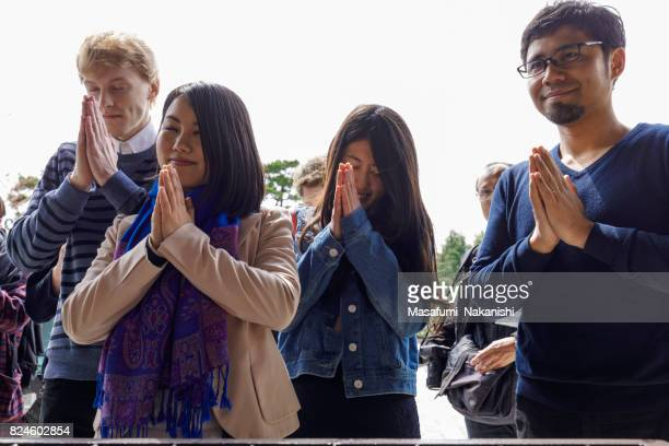 multinational people praying in japanese temples - invocation stock photos and pictures