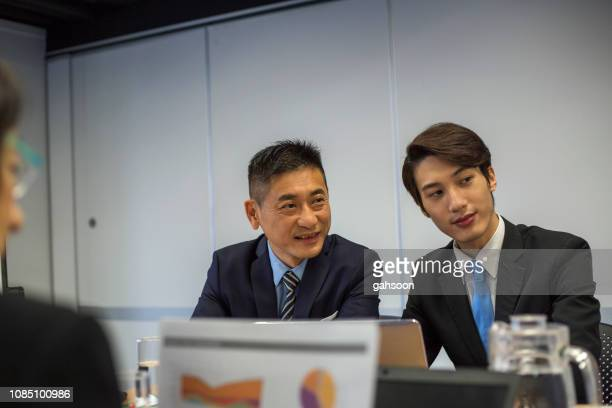 multiple aged group of asian businesspeople working together in a meeting and presentation, confident japanese business colleagues sitting at board room having discssion - economist stock pictures, royalty-free photos & images