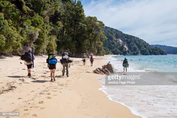 Multiple backpackers walking along a beach