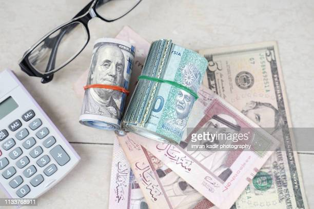 multiple banknote on wooden table - gulf countries stock pictures, royalty-free photos & images